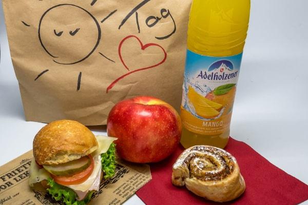 Lunch-Pakete Beispiel: belegte Semmel, Apfel, Mini-Plundetteilchen und Getränk